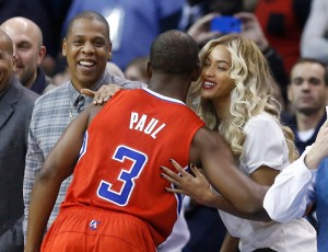 Los Angeles Clippers guard Chris Paul (3) greets Jay-Z, left, and Beyonce, right, before the start of an NBA basketball game against the Oklahoma City Thunder in Oklahoma City, Thursday, Nov. 21, 2013. (AP Photo/Sue Ogrocki)